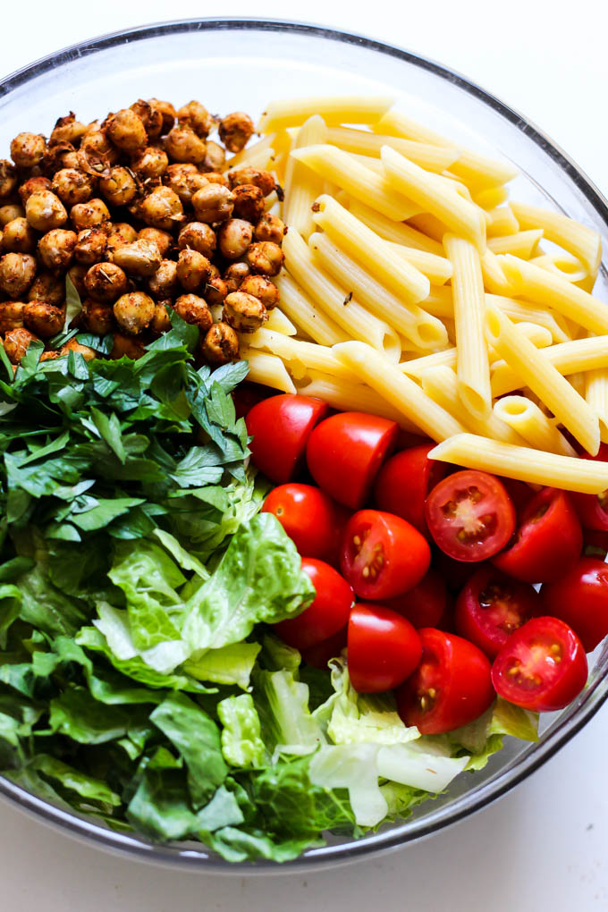 A mixing bowl filled with chopped romaine, parsley, tomatoes, roasted chickpeas and penne pasta