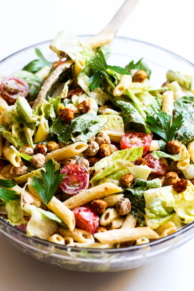 A large bowl of mixed caesar pasta salad
