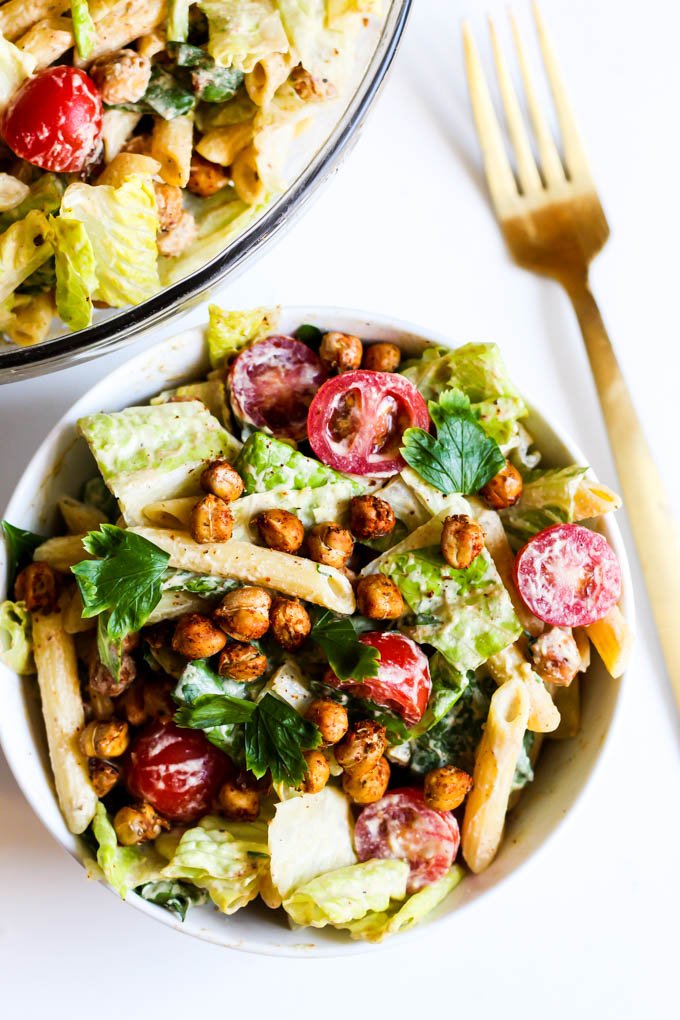 A single serving of plant-based caesar pasta salad topped off with roasted chickpeas