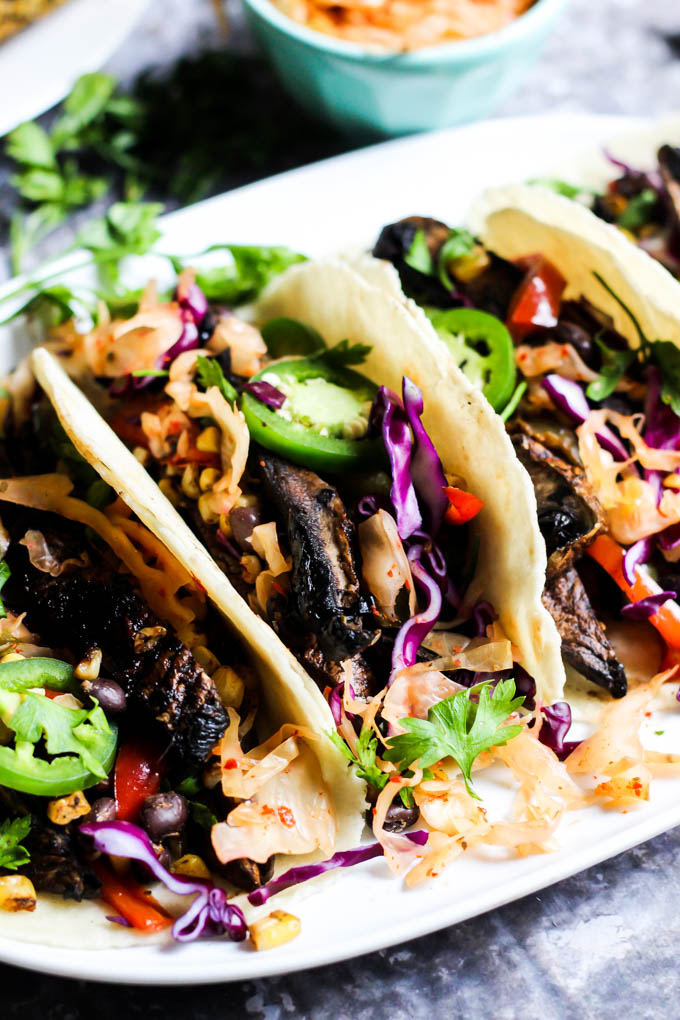a white serving platter with three mushroom tacos topped with cabbage and jalapenos