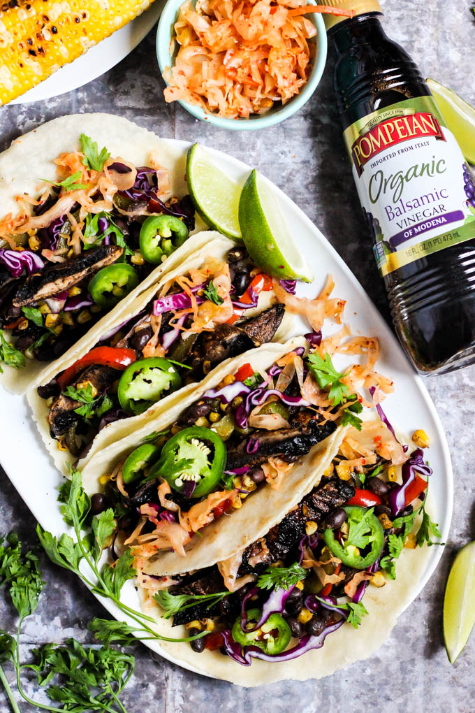a platter of mushroom tacos served with cilantro, kimchi, corn and limes alongside a bottle of balsamic vinegar
