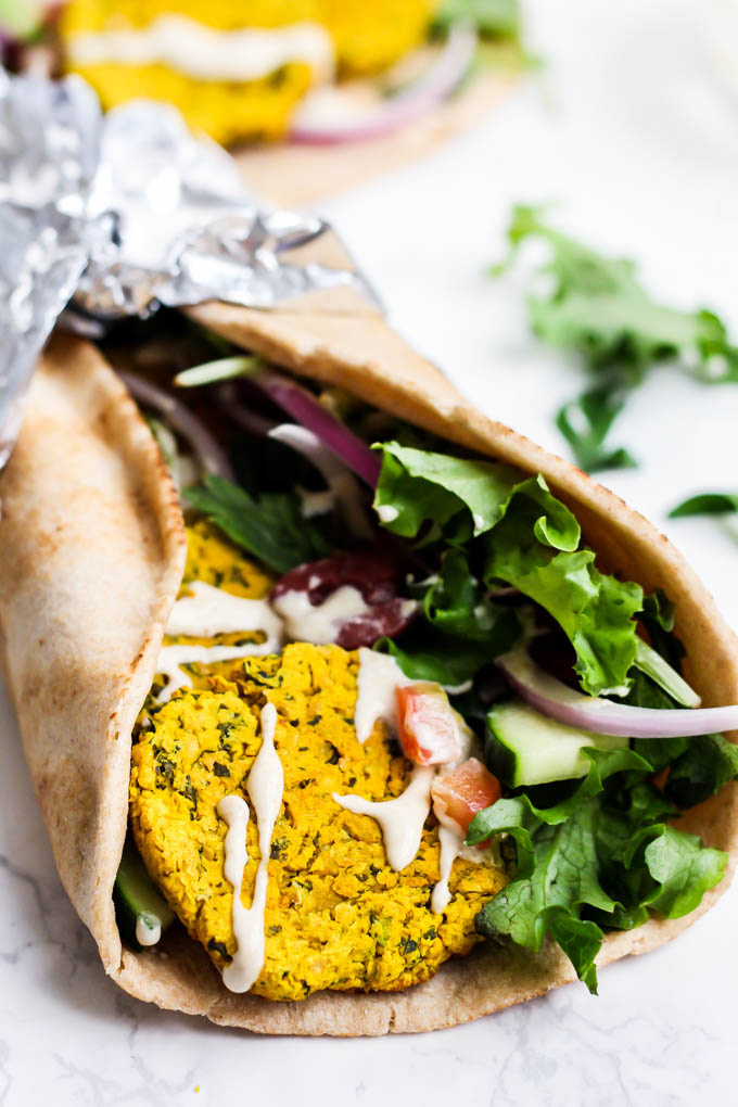 a falafel wrap with greens and a drizzle of tahini