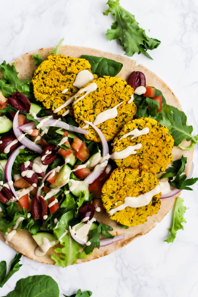 an openfaced pita sandwiched with 4 falafels, veggies, greens and tahini