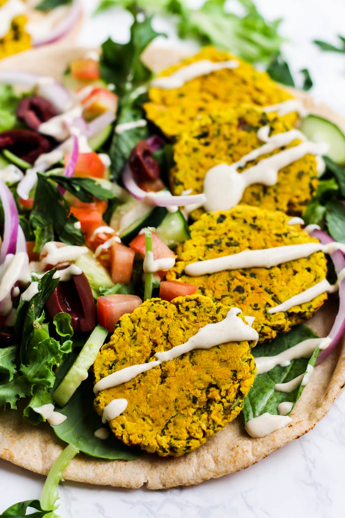 a close up of a pita topped with four turmeric falafels with veggies and tahini