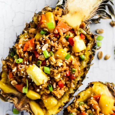 A hollow half of a pineapple serving fried rice
