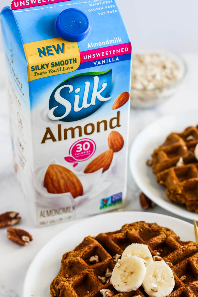 a carton of almond milk next to a plate of waffles