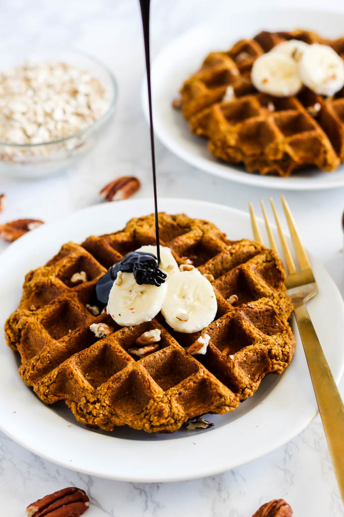 a waffle topped with sliced bananas and pecans being drizzled with molasses