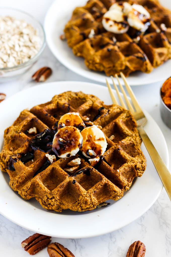 two waffles each topped with sliced bananas, chopped pecans and molasses