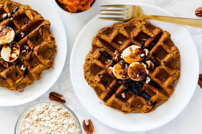 two pumpkin waffles topped with bananas, pecans and molasses