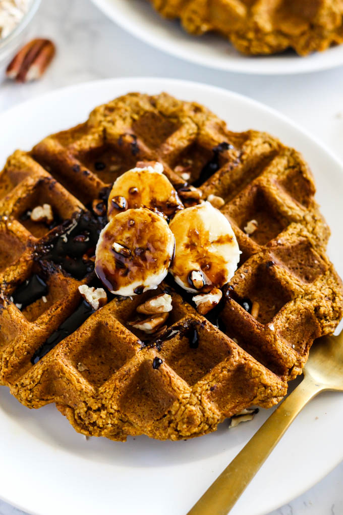 a plate with a pumpkin waffled topped with bananas, pecans and molasses