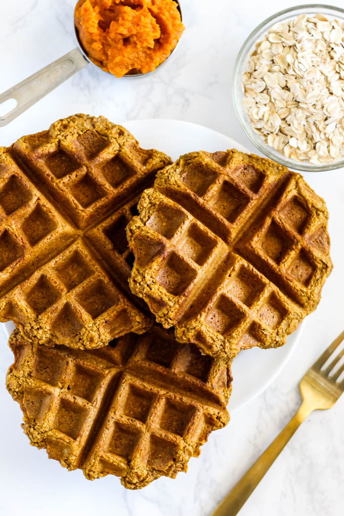 three pumpkin waffles on a plate next to a bowl of oats and a measuring cup of pumpkin