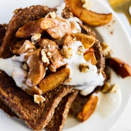 a plate of french toast topped with apples, walnuts and vegan yogurt