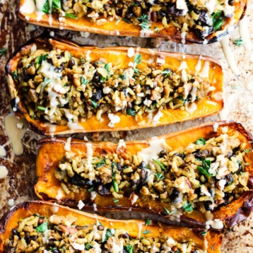a tray of stuffed squash topped with tahini