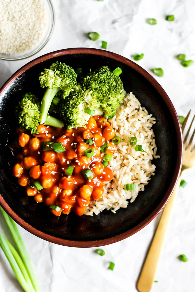 A bowl of broccoli and brown rice topped with sweet and sour chickpeas and green onion