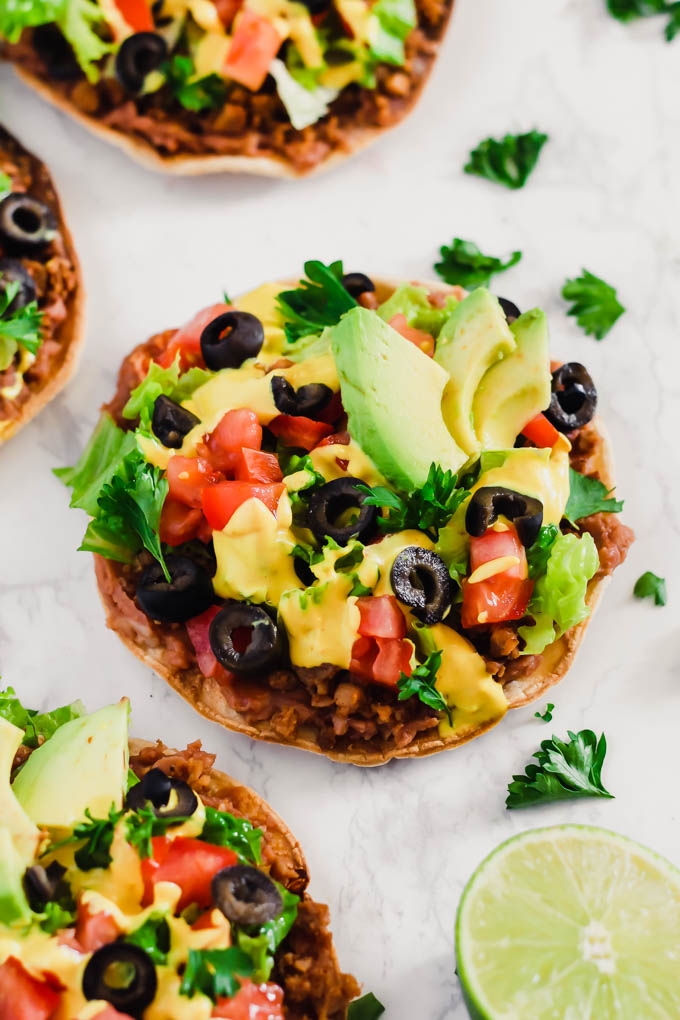 These Vegan Seven Layer Tostadas are loaded with all of your favorite taco toppings like beans, cashew cheese and avocado! A healthy 30-minute meal great for busy weeknights or for serving a crowd.