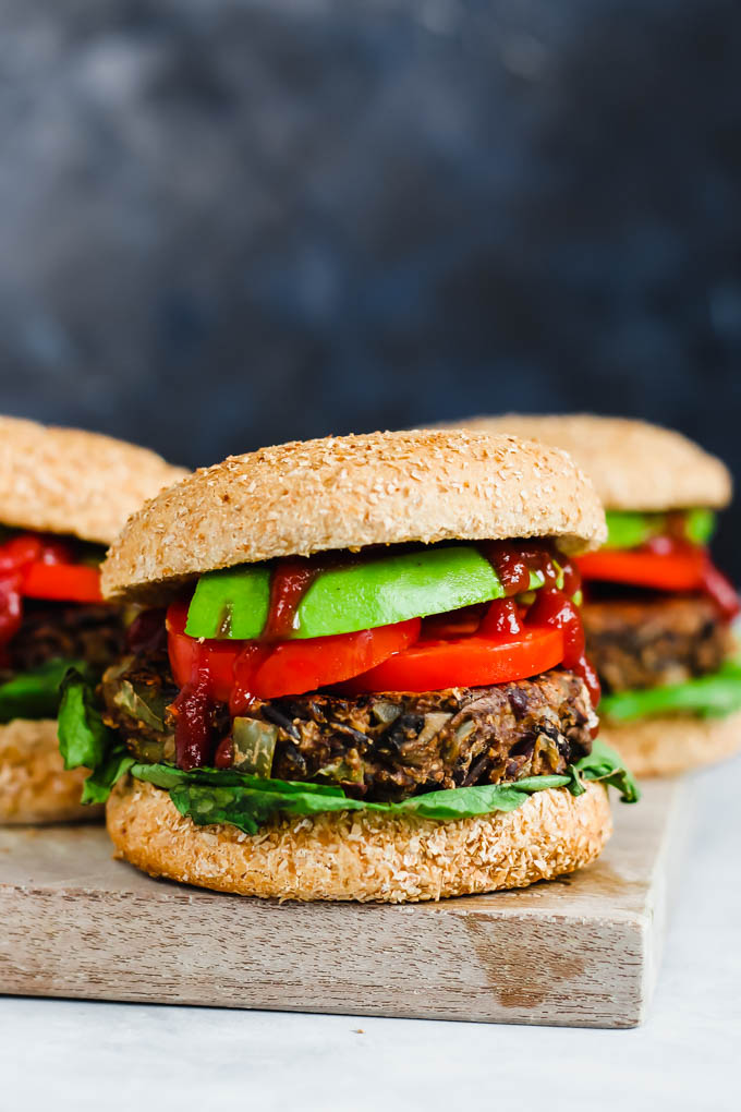A straight-on shot of three wild rice mushroom veggie burgers piled high with ketchup, avocado, lettuce and tomato slices