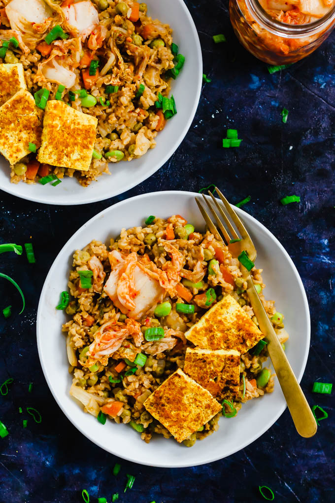 An overhead shot of two bowls of korean kimchi fried rice topped with tofu and green onions