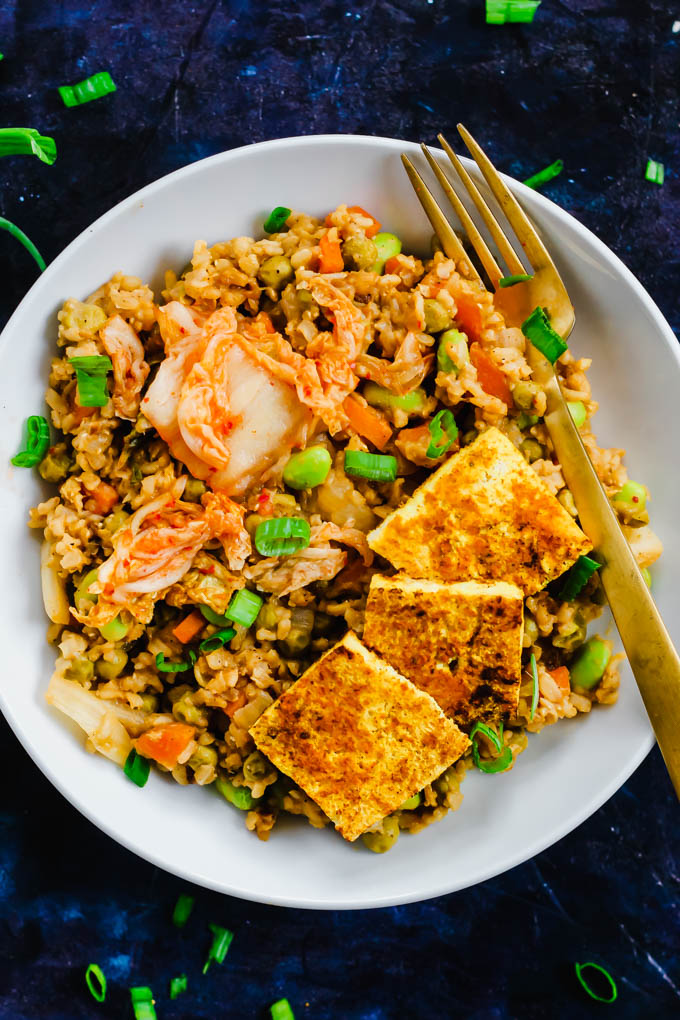 A bowl of kimchi fried rice served with green onions and tofu