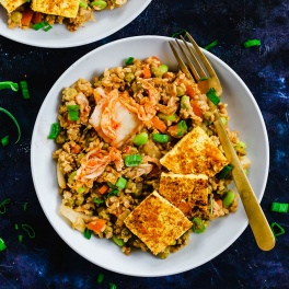 A bowl of vegan kimchi fried rice topped with green onions