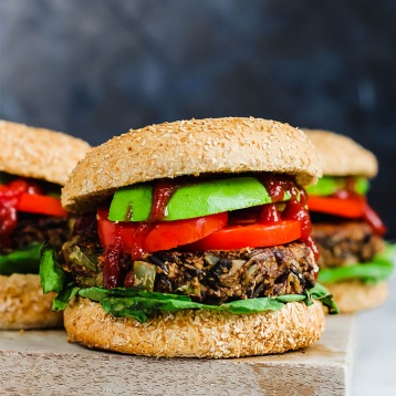 Three wild rice mushroom veggie burgers on a wooden cutting board topped with ketchup, avocado, lettuce and tomato