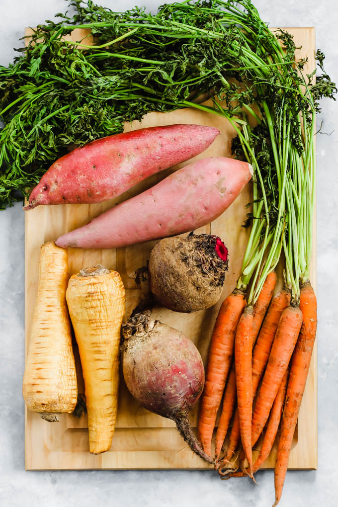These Roasted Root Vegetables make a colorful side dish for the holidays or any weeknight dinner. To top it off, we're making a flavorful carrot top chimichurri full of healthy fats!
