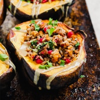 a close up shot of a stuffed acorn squash filled with wild rice, tempeh and pomegranate seeds