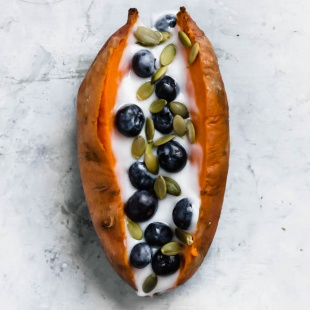 a baked sweet potato topped with vegan yogurt, blueberries and pumpkin seeds