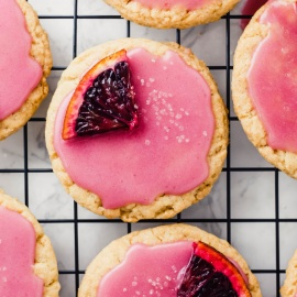 a vegan sugar cookie with blood orange glaze topped with an orange segment and a sprinkle of sugar