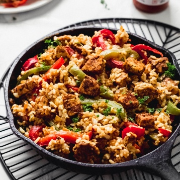 A cast iron skillet serving vegan cajun rice and fried tempeh with red and green bell peppers