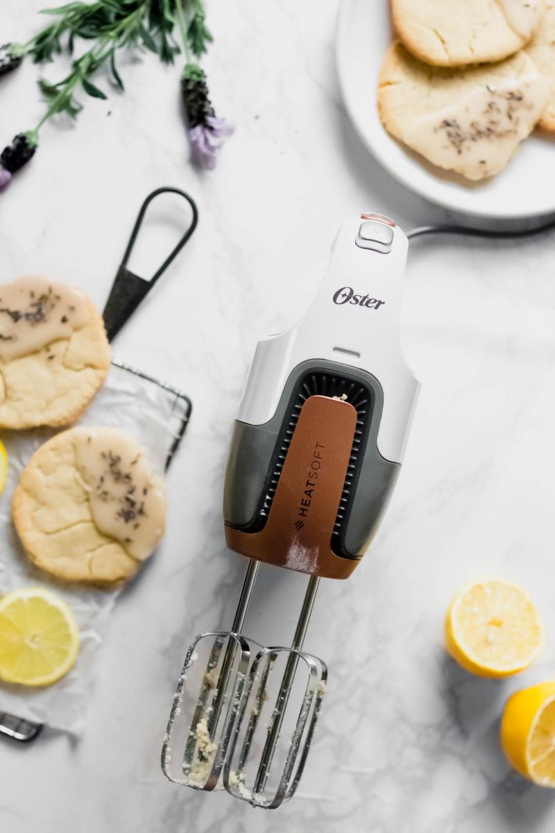 an Oster hand mixer alongside a plate of lemon cookies