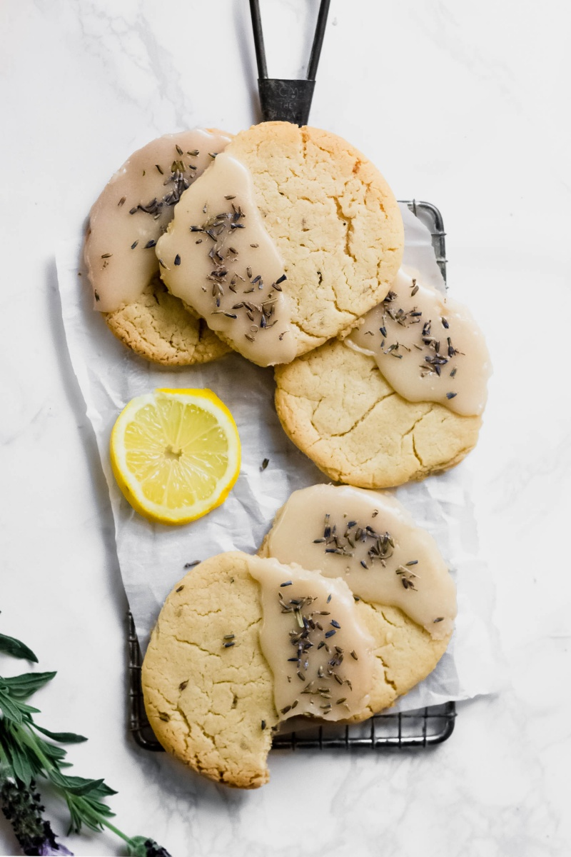 A tray of lavender lemon cookies, one with a bite taken out of it