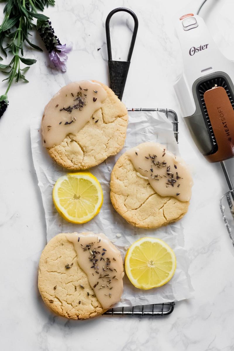 a tray of three lavender lemon cookies served alongside lemon slices