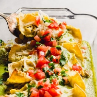 a spatula digs into a dish of vegan enchiladas
