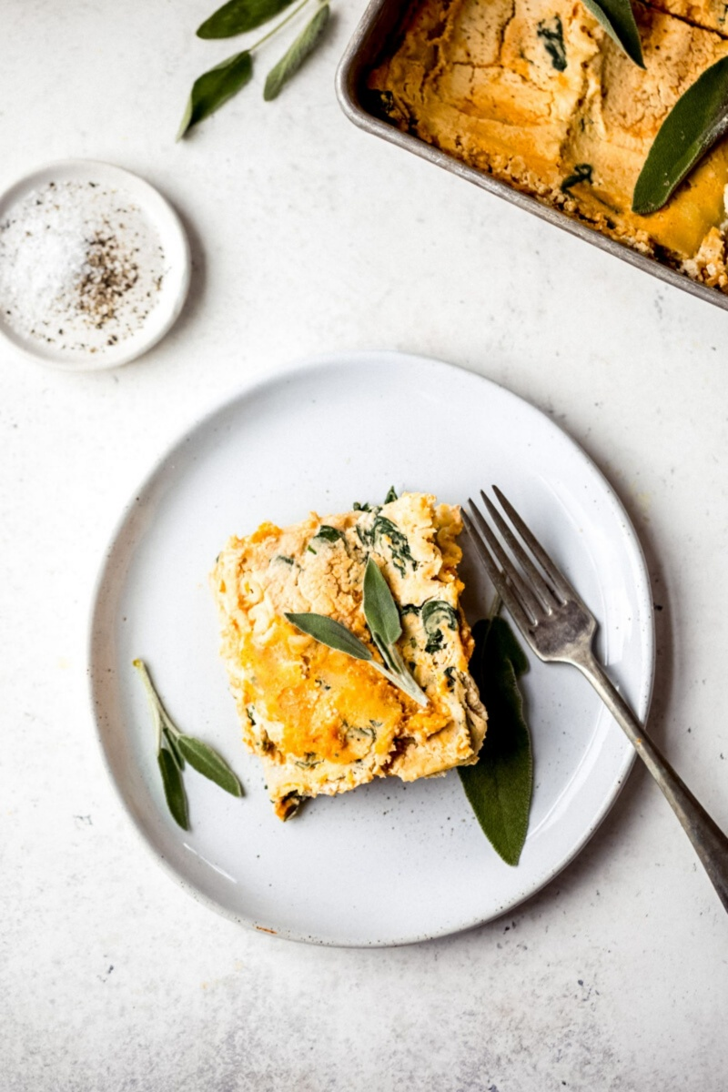slice of butternut squash lasagna on a plate with a fork