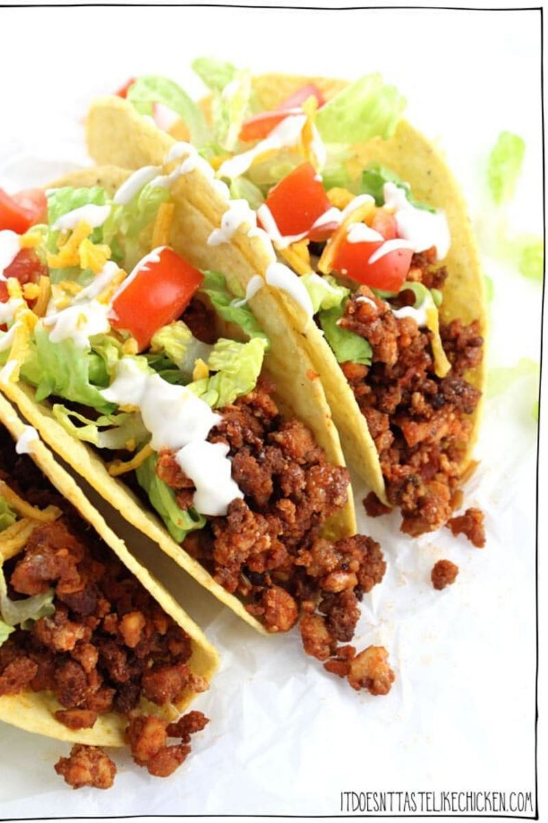 three hard shell tacos with lettuce and tomatoes
