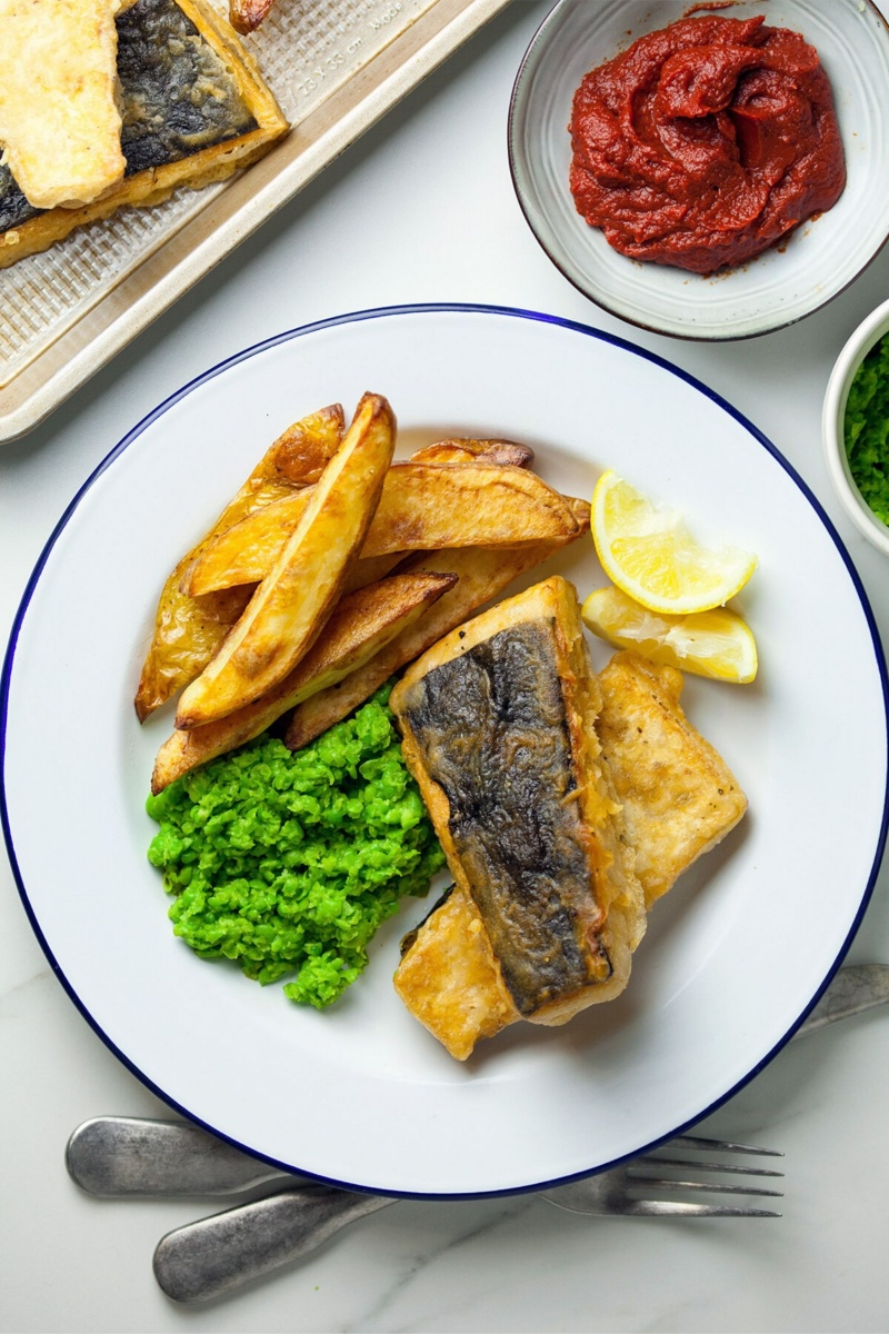 tofu with potato fries on a white plate with a blue border