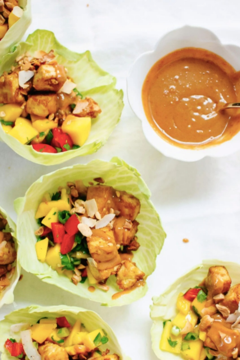 multiple green cabbage wraps with vegetables and tofu with peanut sauce