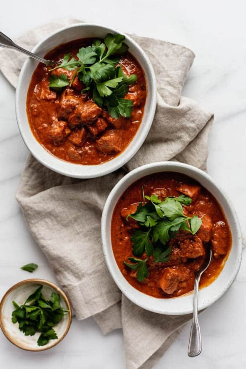 two bowls with red tikka masala topped with cilantro