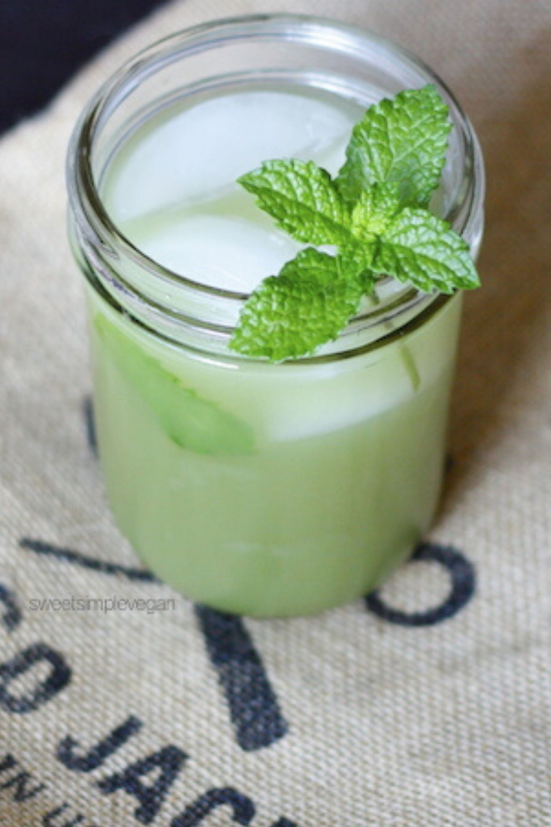 glass with ice and green drink topped with mint sprig