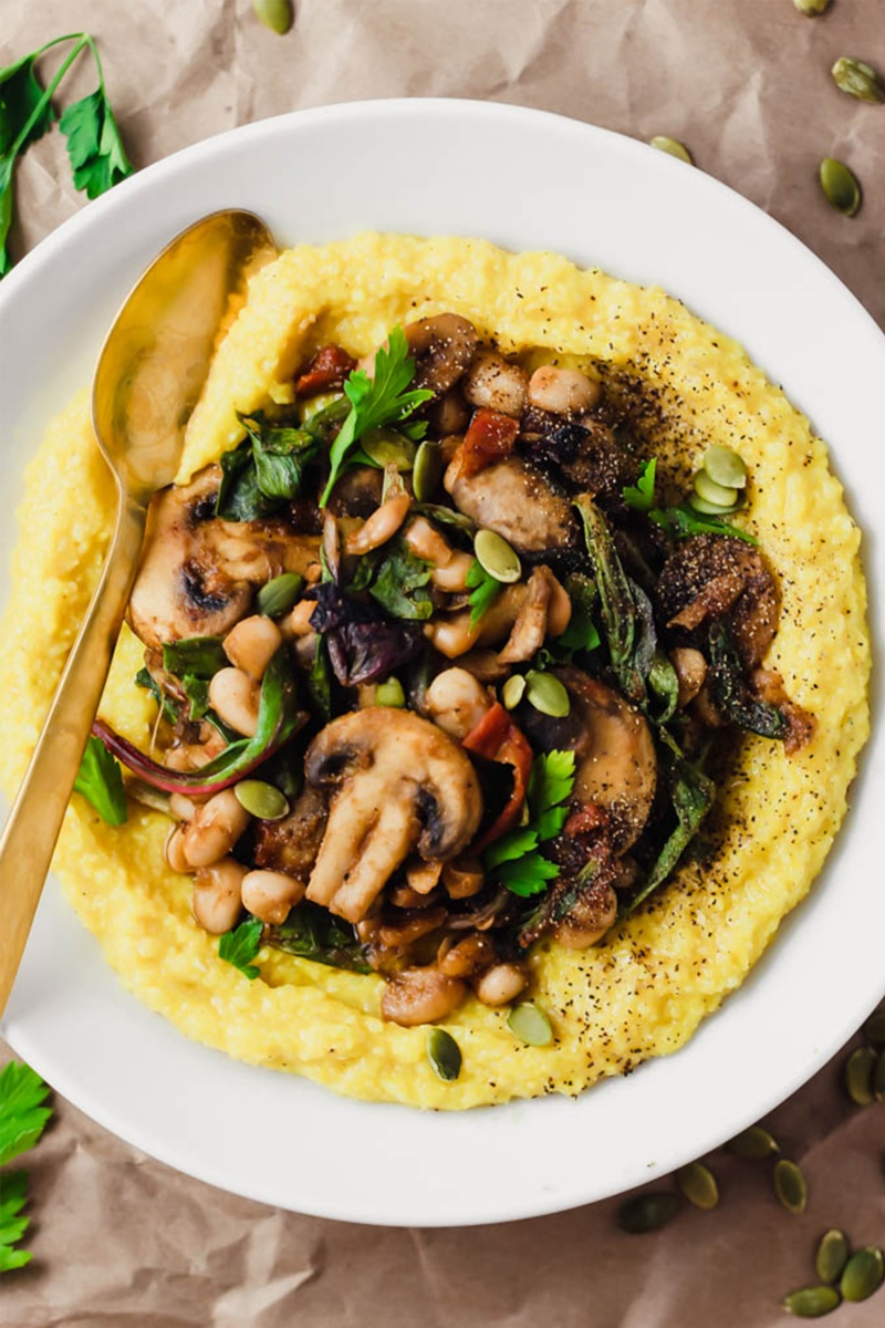 brown paper bag background with white bowl of yelllow polenta and mushrooms on top
