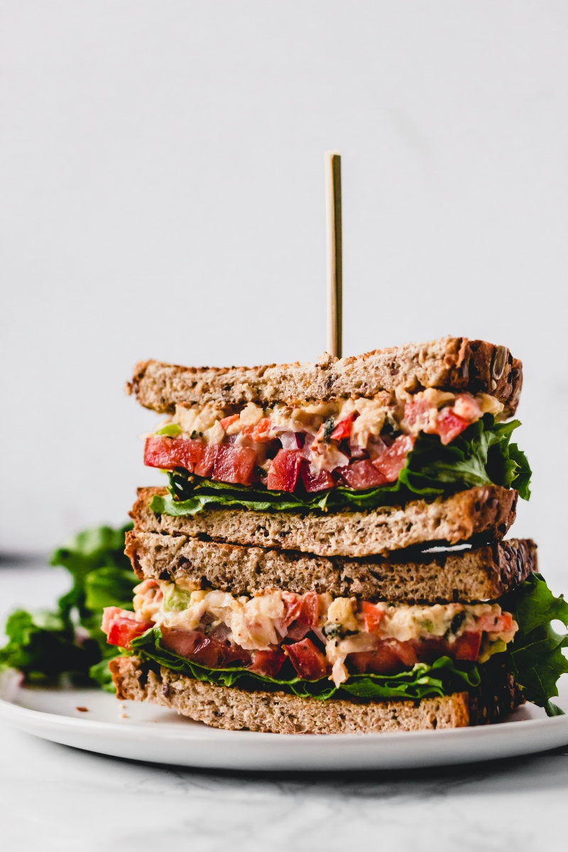 stack of two skewered vegan sandwiches with vegetables and lettuce