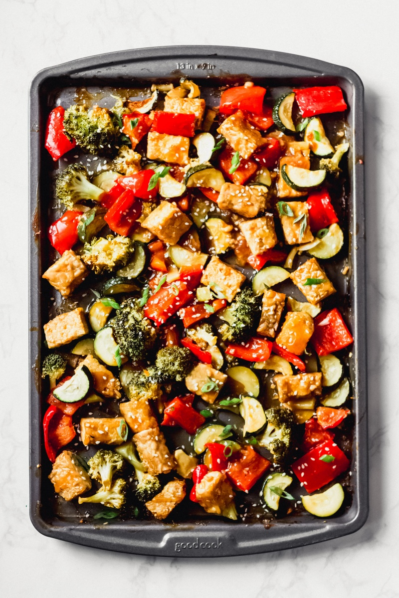 a sheet tray of cooked tempeh and vegetables topped with sesame seeds