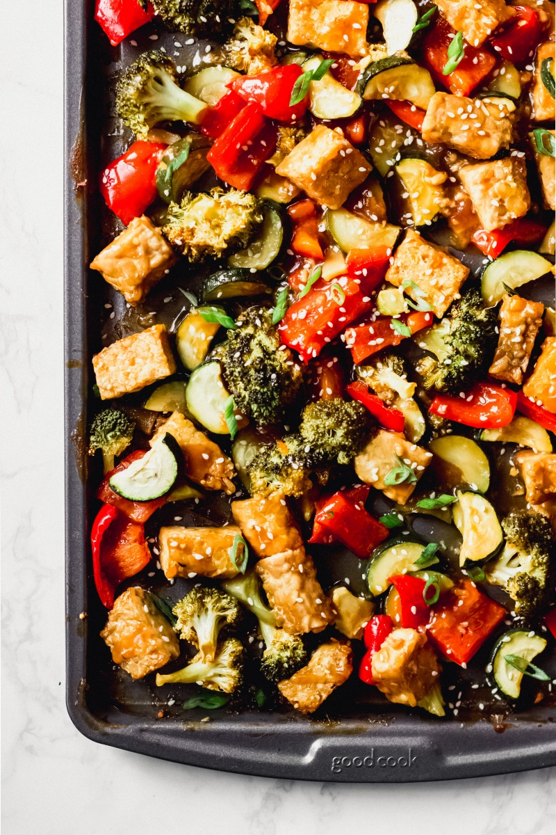 a sheet tray full of roasted tempeh and vegetables topped with sesame seeds