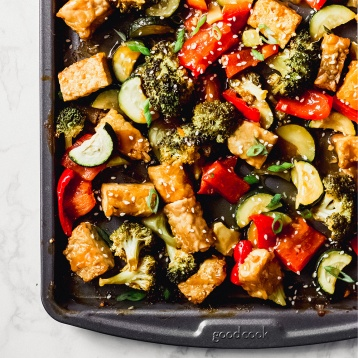 a sheet tray of cubed tempeh and roasted vegetables topped with sesame seeds