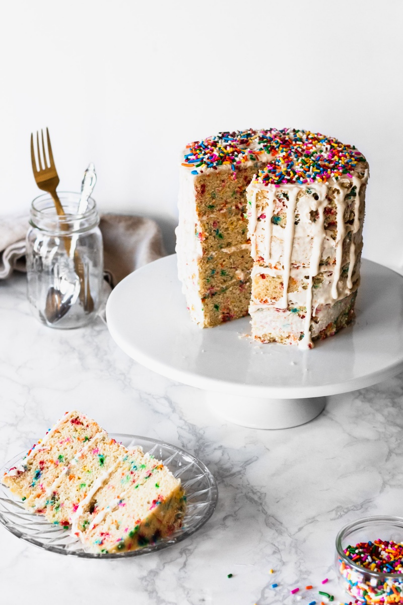 vegan funfetti cake on a white cake stand with a marble backdrop