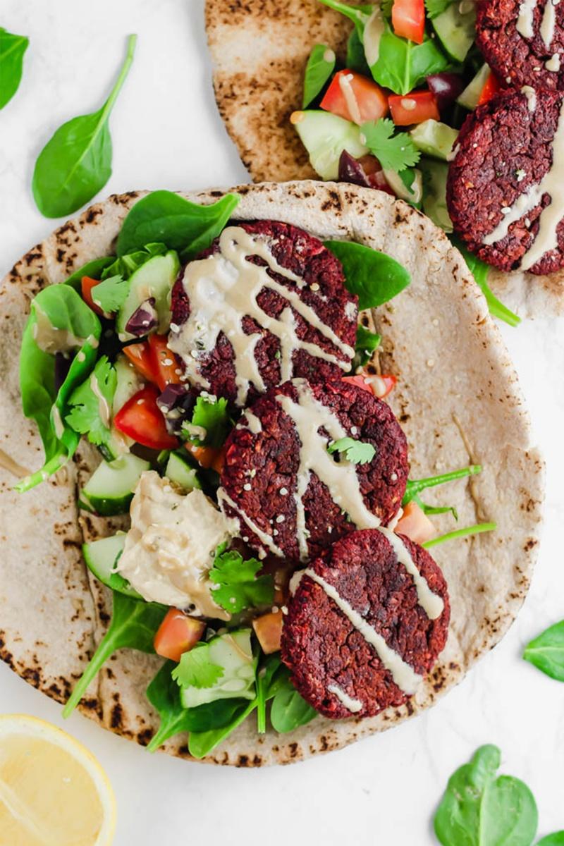 flat lay pita with pink beet falafel and tahini sauce