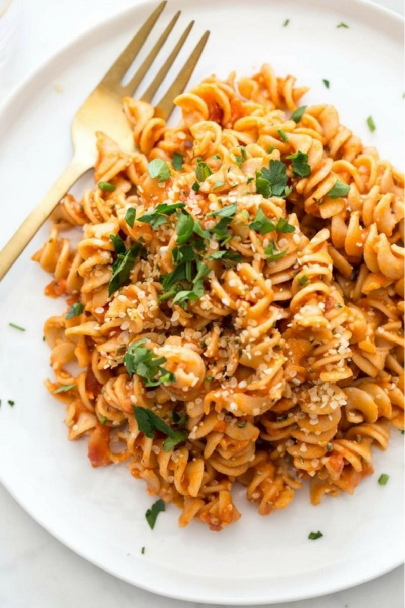 white plate of red rotini pasta