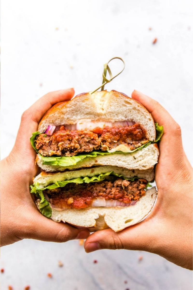 hands holding large vegan pizza burger