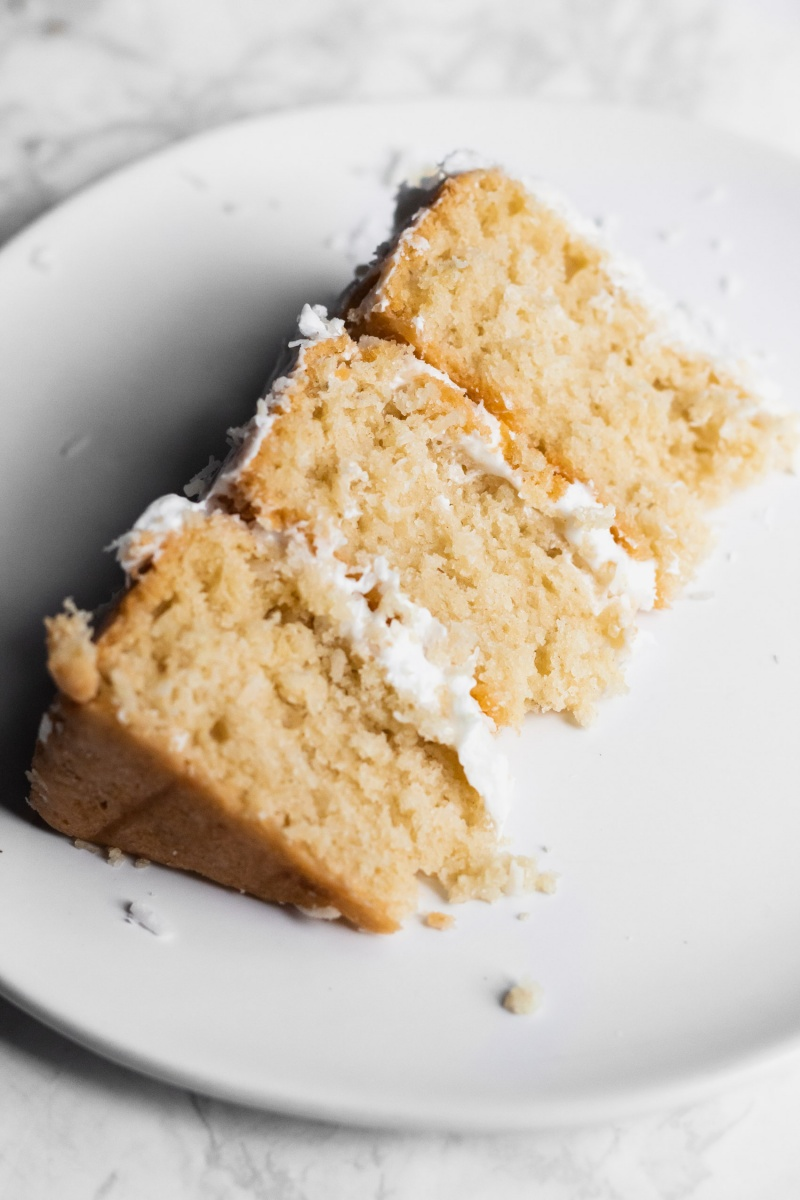 one slice of vegan coconut cake on white plate