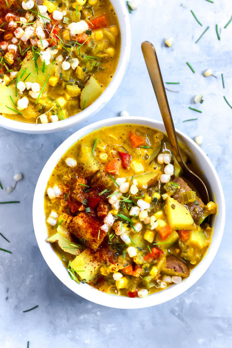 vegan soup with corn and potatoes with a gold spoon